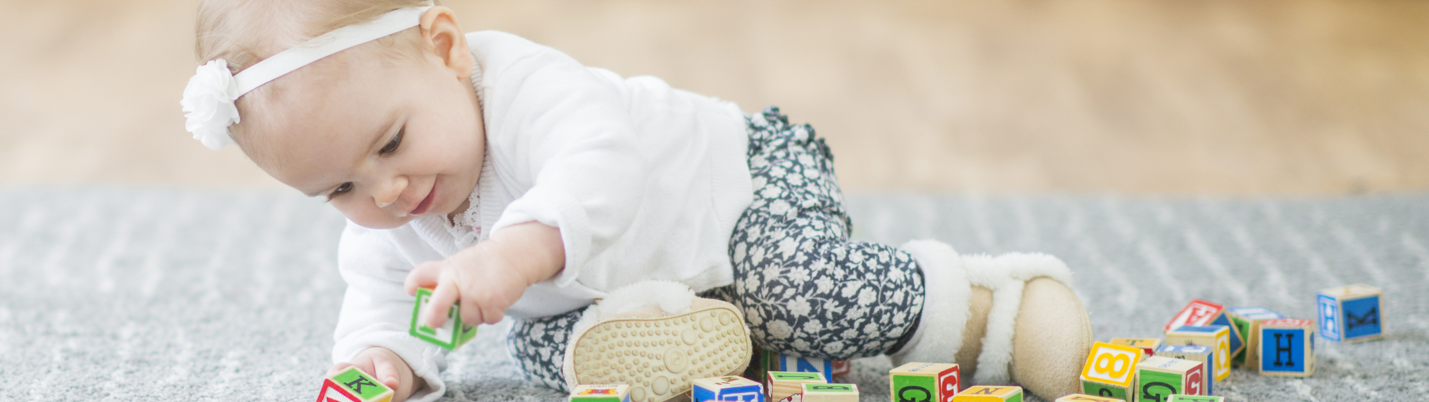 Baby girl lying on a rug playing with wood letter blocks