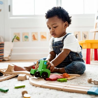 Toddler boy sitting on the floor pusing a wooden truck.