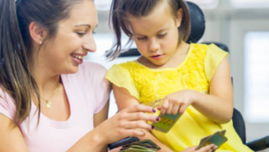 Preschool teacher and girl in wheelchair looking at a card.