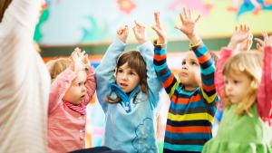 Teacher and children at group time raising arms overhead.