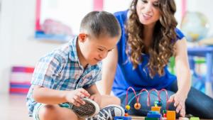 Hispanic boy with Down Syndrome reaching for toys as daycare worker watches
