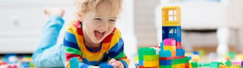 Toddler boy laughing and playing with legos on the floor