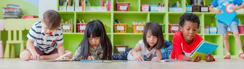 Four young children lying on the floor looking at books.